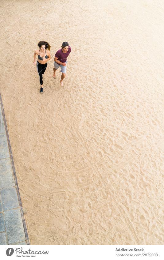 Paar, das am Strand läuft. Mensch sportlich rennen Training Aktion Joggen Fitness Küste Läufer Zusammensein Geschwindigkeit Außenaufnahme Wellness Sand Bewegung