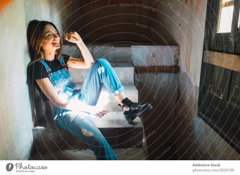 Lächelnde Frau auf der Treppe Gebäude heiter sitzen Freitreppe Erholung