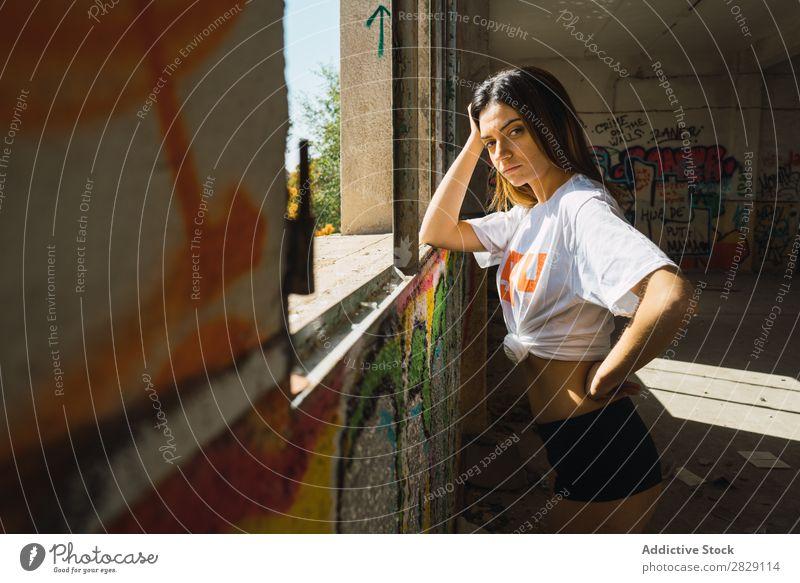 Lächelnde Frau in verlassenem Raum mit Graffiti heiter Körperhaltung Blick in die Kamera Glück Jugendliche mehrfarbig