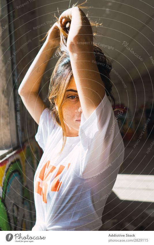 Lächelnde Frau in verlassenem Raum mit Graffiti heiter Körperhaltung Blick in die Kamera Jugendliche mehrfarbig