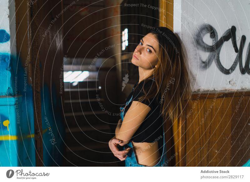 Frau, die in einem verlassenen Gebäude posiert. heiter Körperhaltung Graffiti attraktiv genießen Behaarung