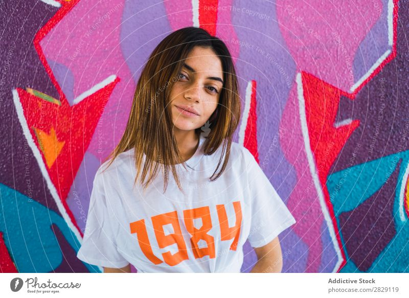 Lächelnde Frau in verlassenem Raum mit Graffiti heiter Körperhaltung Blick in die Kamera Glück Jugendliche