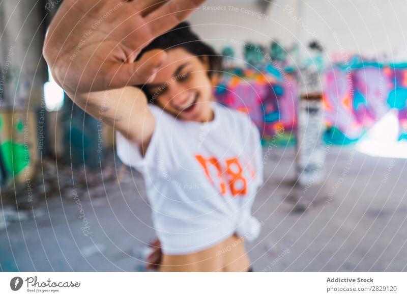 Lächelnde Frau in verlassenem Raum mit Graffiti heiter Körperhaltung Glück Jugendliche mehrfarbig