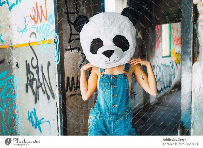 Oben ohne Frau in einem verlassenen Gebäude mit Plüsch-Pandakopf. Körperhaltung Erotik heiß genießen attraktiv deckend