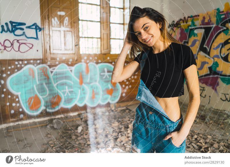 Frau, die in einem verlassenen Gebäude posiert. Lächeln heiter Körperhaltung Graffiti attraktiv genießen