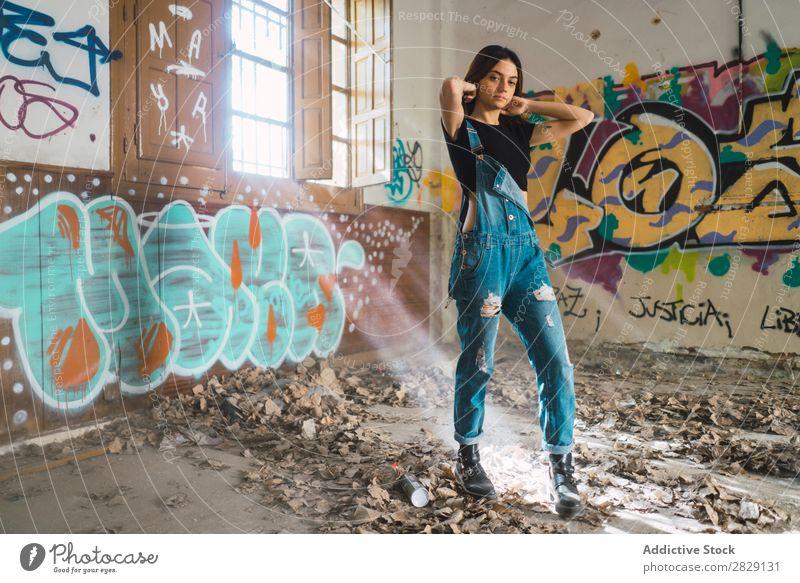 Frau setzt Haare in verlassenem Gebäude Lächeln heiter Körperhaltung Blick in die Kamera Graffiti attraktiv