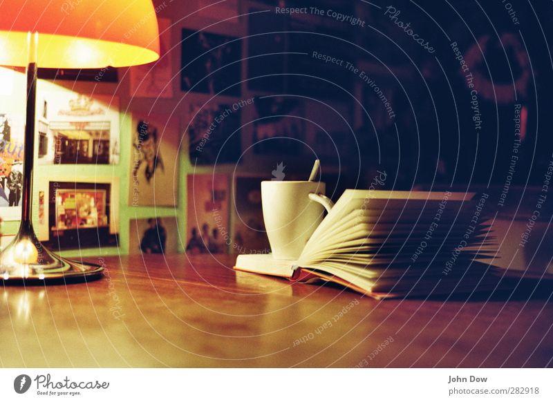 Gute-Nacht-Geschichte Erholung Denken Buch Lifestyle Häusliches Leben Tisch lesen trinken Küche Müdigkeit Tasse gemütlich Buchseite Printmedien heimelig Tischlampe