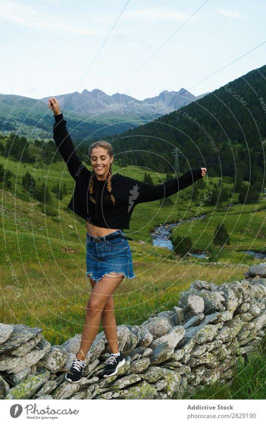 Hübsche Frau, die auf einer Felswand läuft. laufen Wiese Felsen Wand Gleichgewicht Hände hoch Mädchen Jugendliche schön Sommer Natur Beautyfotografie Gras