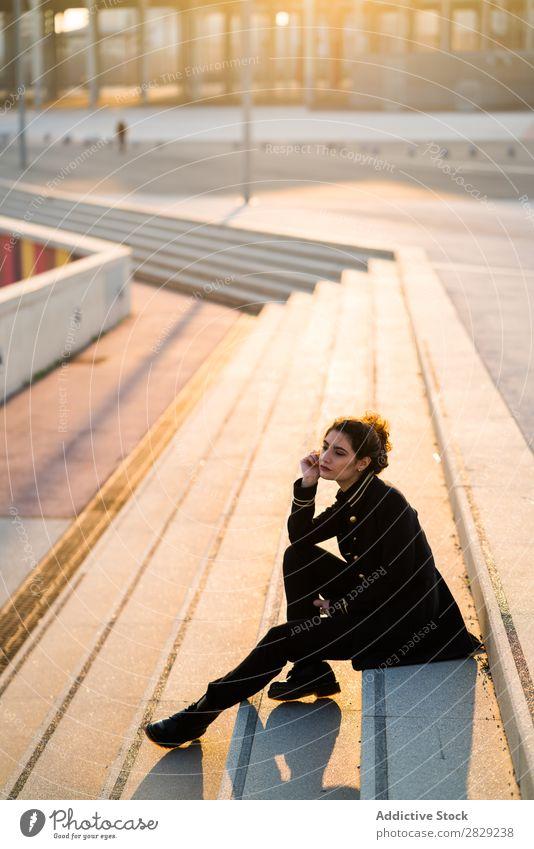 Attraktive Frau auf der Treppe sitzen Wegsehen lässig Bekleidung selbstbewußt Stil ernst Jugendliche Behaarung schön Mädchen attraktiv Glamour Dame traumhaft