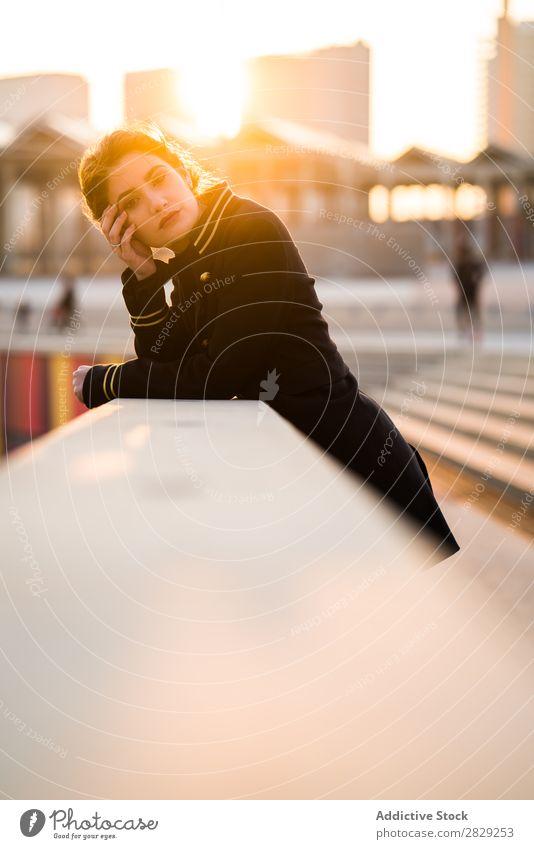 Selbstbewusste Frau, die vor der Kamera steht. Haltekopf Geländer Sonnenuntergang selbstbewußt Blick in die Kamera lässig Bekleidung Stil ernst Jugendliche