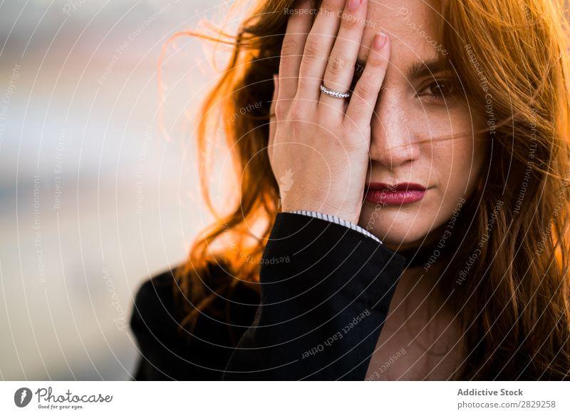 Frau, die das Gesicht mit der Hand schließt. selbstbewußt Auge schließen Sonnenuntergang Blick in die Kamera lässig Bekleidung Stil ernst Jugendliche schön