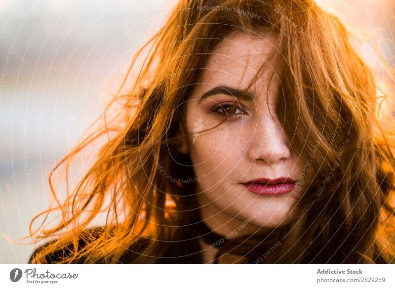Porträt einer ernsthaften jungen Frau, die mit fliegenden Haaren in die Kamera schaut. Sonnenuntergang Behaarung selbstbewusst in die Kamera schauen lässig