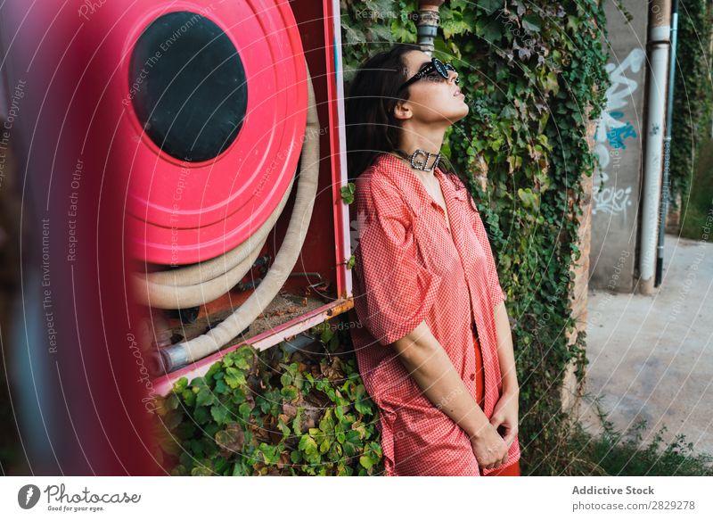 Frau, die am Feuerwehrschlauch posiert. Stil Straße Stadt Löschschlauch rot Körperhaltung Pflanze Wachstum Sonnenbrille Porträt attraktiv Beautyfotografie