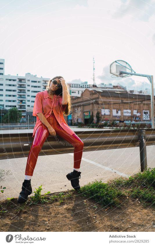 Frau, die auf dem Spielplatz in einem Zaun sitzt. Stil Straße Stadt Körperhaltung Sonnenbrille Porträt attraktiv Beautyfotografie trendy Lifestyle hübsch Mode