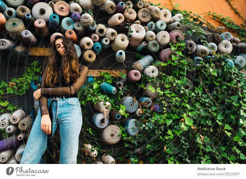 Frau an der Wand mit Rollen Stil Straße Pflanze Walze Sträucher Stadt Körperhaltung Porträt attraktiv Beautyfotografie trendy Lifestyle hübsch Mode Jugendliche