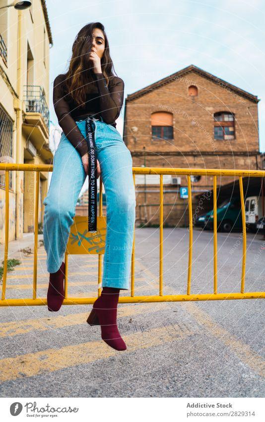 Frau am Zaun sitzend Stil Straße Stadt Körperhaltung Asphalt Porträt attraktiv Beautyfotografie trendy Lifestyle hübsch Mode Jugendliche Model schön Dame
