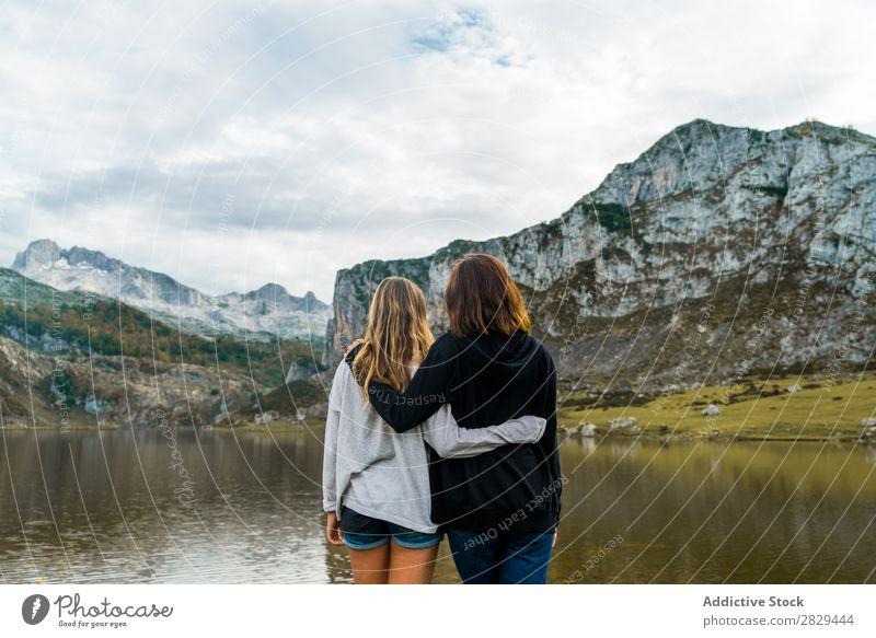 Frauen am See stehend Wiese umarmend Zusammensein Freundschaft Erholung Berge u. Gebirge Natur Feld Mädchen Gras schön Jugendliche grün Frühling Mensch