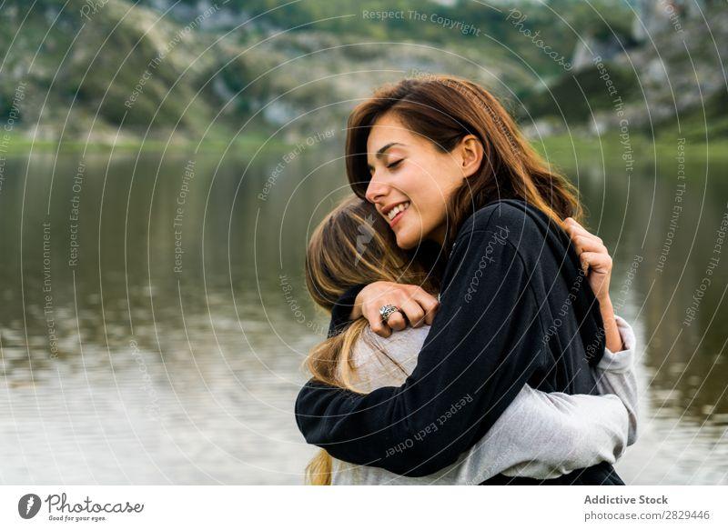 Mädchen umarmen sich am See Frau Wiese umarmend stehen Zusammensein Freundschaft Erholung Berge u. Gebirge Natur Feld Gras schön Jugendliche grün Frühling