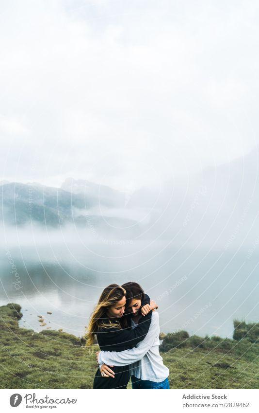 Frauen am nebligen See Wiese umarmend Nebel stehen Zusammensein Freundschaft Erholung Berge u. Gebirge Natur Feld Mädchen Gras schön Jugendliche grün Frühling