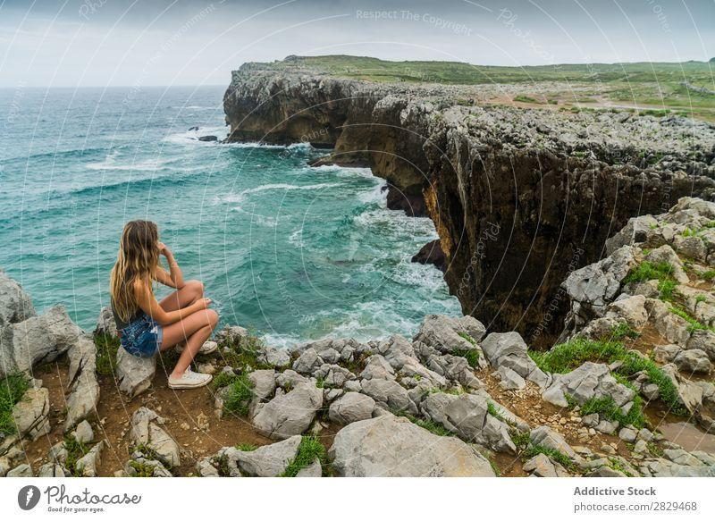Frau, die auf einer Klippe sitzt. Meer sitzen schön Felsen Sommer Natur Ferien & Urlaub & Reisen Wasser Landschaft Jugendliche blau Lifestyle Freiheit wandern