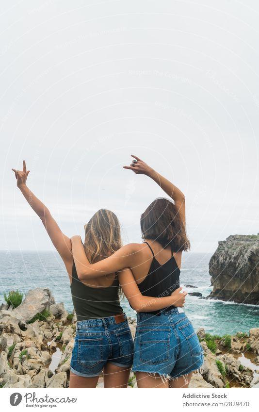 Frauen mit erhobenen Armen, die auf der Klippe stehen. Meer schön Felsen Sommer Natur Ferien & Urlaub & Reisen Wasser Landschaft Jugendliche blau Lifestyle