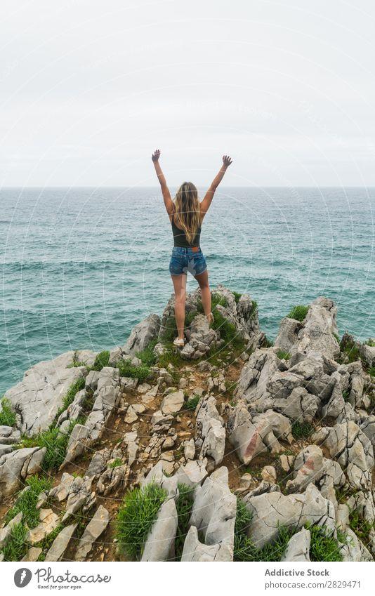 Mädchen mit erhobenen Armen, stehend auf der Klippe. Frau Meer schön Felsen Sommer Natur Ferien & Urlaub & Reisen Wasser Landschaft Jugendliche blau Lifestyle