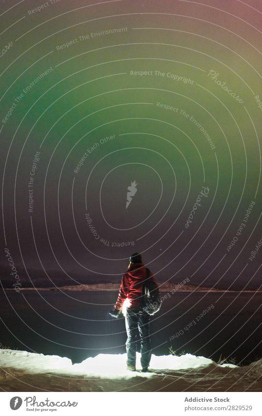 Stehende Person am zugefrorenen See Winter Natur kalt Norden Mensch Tourist Rucksack Polarlicht Nacht Wasser bedeckt Schnee Jahreszeiten weiß Landschaft Eis