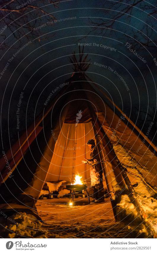 Mann wärmt sich im Zelt auf Winter Natur kalt Norden bedeckt Licht Nacht Freudenfeuer Mensch Erwärmung stehen Tourist Reisender Wald Schnee Jahreszeiten weiß
