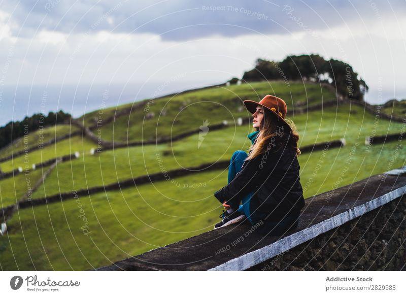 Frau sitzt auf einem Zaun auf dem Feld. sitzen grün Natur Wiese Erholung ruhen Wegsehen Hut Frühling Sommer Gras Landschaft Landwirtschaft ländlich Sonnenlicht