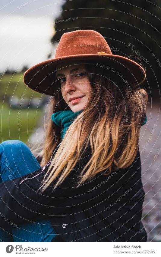 Frau sitzt auf einem Zaun auf dem Feld. sitzen grün Natur Wiese Erholung ruhen Hut Frühling Sommer Gras Landschaft Landwirtschaft ländlich Sonnenlicht Bauernhof