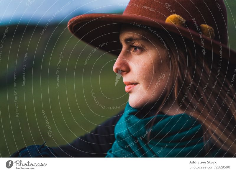 Verträumte Frau, die am Zaun auf dem Feld steht. sitzen grün Natur Wiese stehen träumen Erholung ruhen Wegsehen Hut Frühling Sommer Gras Landschaft