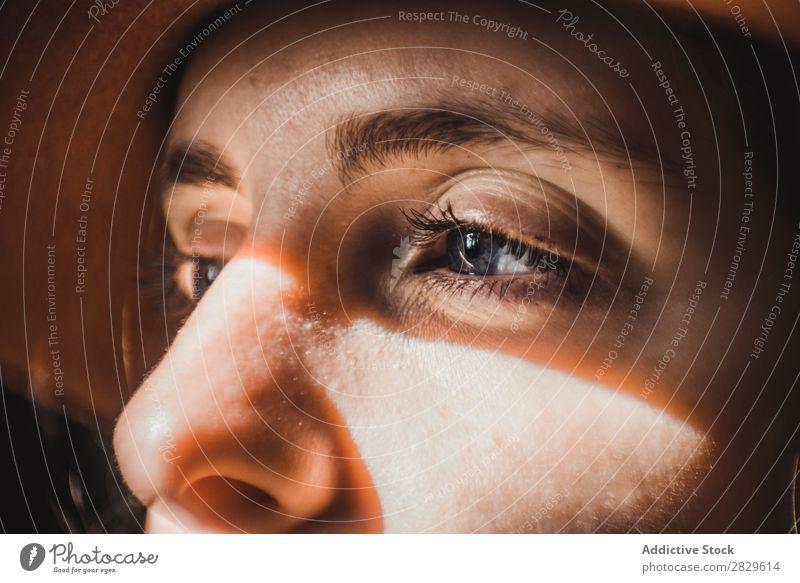 Frau mit Leuchtgeschossen im Gesicht Lichtschein Auge Nahaufnahme Jugendliche Porträt schön