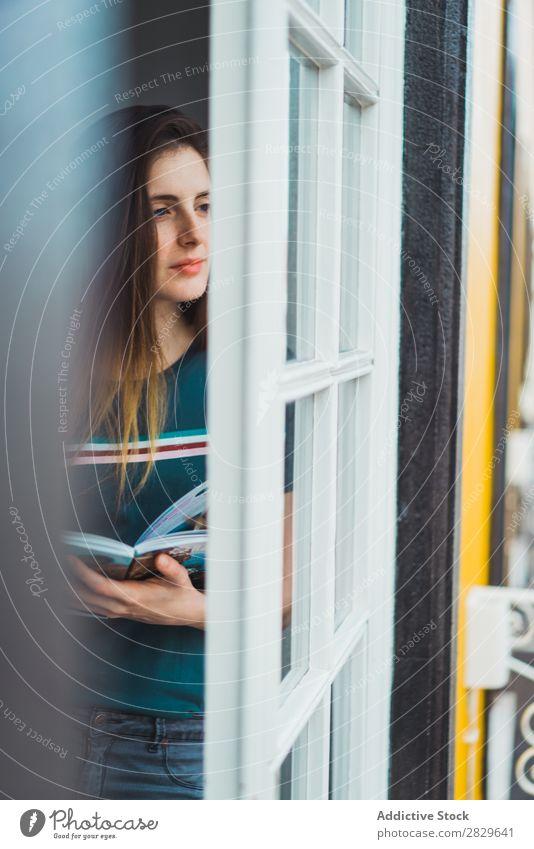 Träumendes Mädchen, das durchs Fenster wegblickt. Frau träumen Beautyfotografie Porträt schön besinnlich genießen Reflexion & Spiegelung Denken Erholung