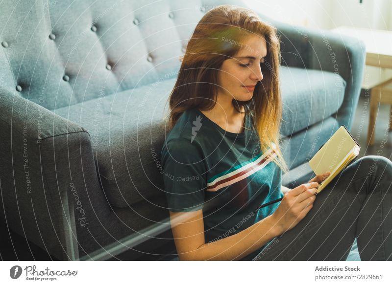 Junge Frau auf dem Boden sitzend mit Notizblock Notizbuch Freizeit & Hobby Wohnung Planer Schüler Arbeit & Erwerbstätigkeit Lounge freiberuflich Morgen