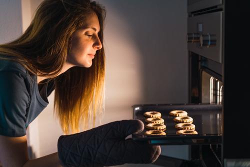 Frau, die Kekse im Ofen macht Herd & Backofen Plätzchen backen Vorbereitung Überprüfung Blechschale frisch Tablett machen Konfekt Wohnung Küche Bäckerei