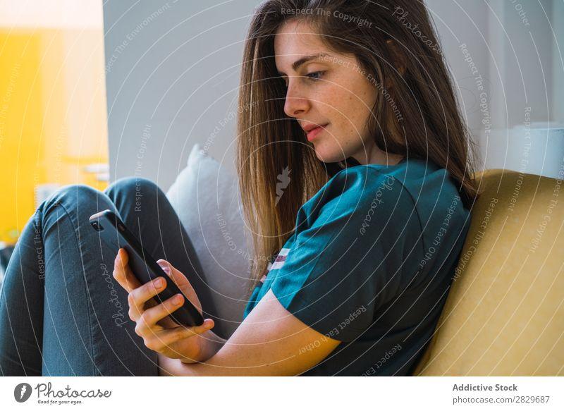 Fröhliches Mädchen mit Telefon, das sich auf dem Sofa entspannt. Frau Liege Lounge PDA Zufriedenheit Fröhlichkeit benutzend Texten Nachrichtenübermittlung