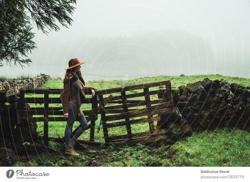 Stylische Frau am Zaun in nebligen Feldern kalt Nebel Stil träumen grün reisend Ferien & Urlaub & Reisen Szene ruhig Ausflugsziel Landwirtschaft Landschaft