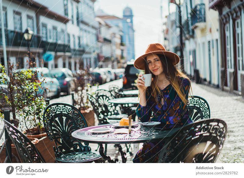 Lächelnde Frau mit Tasse im Außencafé hübsch Stil Straße Hut Kaffee Café Außenaufnahme Mode schön Jugendliche Porträt attraktiv Großstadt Lifestyle Model