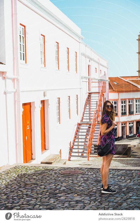 Fröhliche Frau auf der Straße stehend hübsch Stil Sonnenbrille Sonnenstrahlen Außenaufnahme Mode schön Jugendliche Porträt attraktiv Großstadt Lifestyle Model