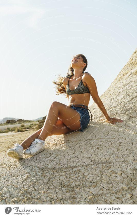 Attraktive Frau auf dem Boden Lächeln sitzen heiter Sand Glück Lifestyle