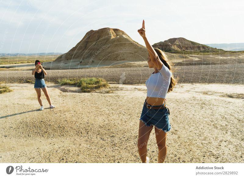 Frau macht Fotos von einer Freundin. Körperhaltung Natur hübsch Hände hoch Lächeln heiter Glück Jugendliche schön natürlich Beautyfotografie Porträt attraktiv