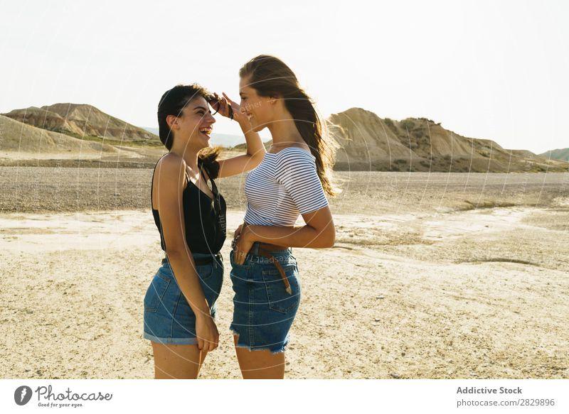 Frauen, die in sandigen Hügeln posieren. Körperhaltung Natur Lächeln heiter Glück Jugendliche schön