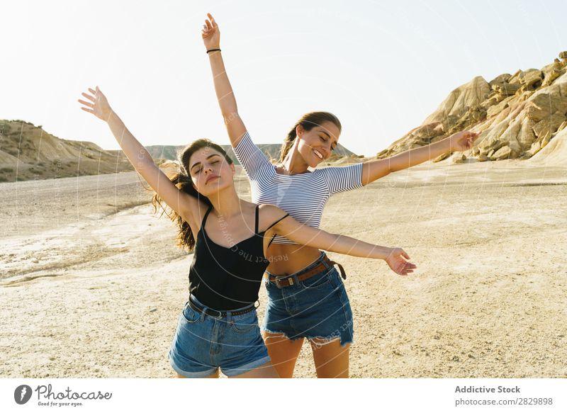 Frauen, die in sandigen Hügeln posieren. Körperhaltung Natur hübsch Augen geschlossen Hände hoch Lächeln heiter Glück Jugendliche schön natürlich