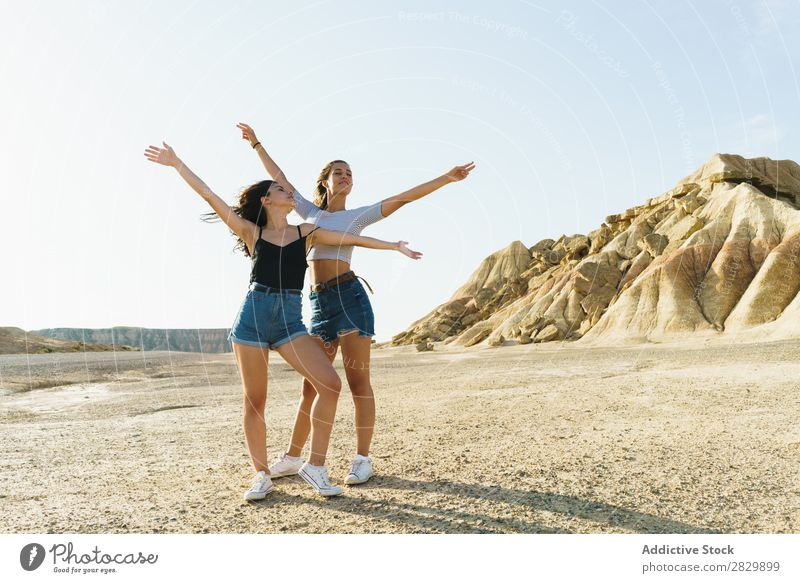Frauen, die in sandigen Hügeln posieren. Körperhaltung Natur Hände hoch Lächeln heiter Glück Jugendliche