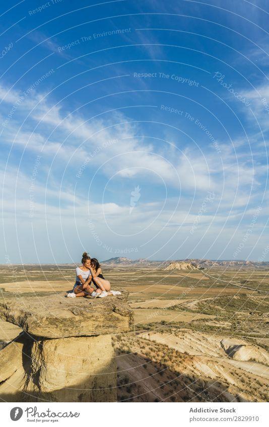 Aufgeregte Frauen, die auf einer Klippe liegen. Erholung Ferien & Urlaub & Reisen Abenteuer Felsen Berge u. Gebirge Tourist Freundschaft Zusammensein Lächeln