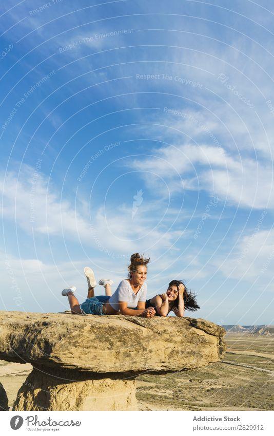 Aufgeregte Frauen, die auf einer Klippe liegen. lügen Erholung Ferien & Urlaub & Reisen Abenteuer Felsen Berge u. Gebirge Tourist Freundschaft Zusammensein