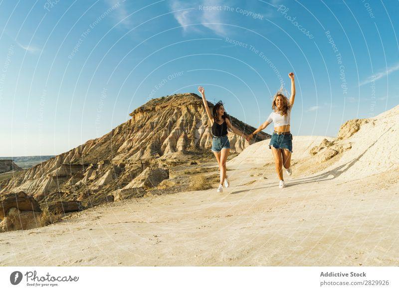 Glückliche Frauen, die auf dem Hügel spazieren gehen. Klippe Aufregung rennen Händchenhalten Freiheit Ferien & Urlaub & Reisen Erfolg Top Berge u. Gebirge