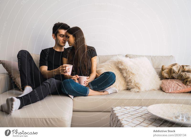 Paar sitzt auf der Couch heimwärts Zusammensein sitzen umarmend Sofa Liege gemütlich Mensch Glück Liebe Haus Mann Frau Lifestyle 2 Jugendliche Erwachsene