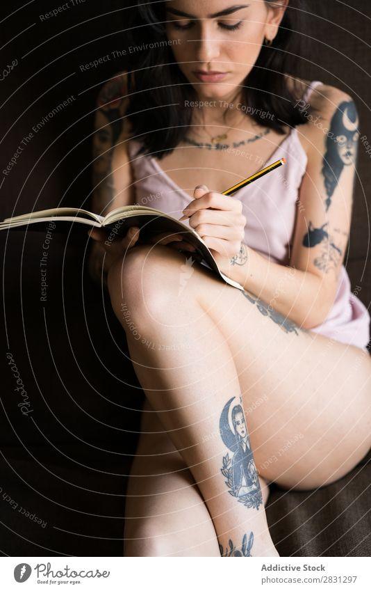 Tätowierte Frau schreibt in Notizbuch heimwärts Bett Tagebuch lässig schreibend Schreibstift Erinnerungen Innenaufnahme Lifestyle Erwachsene tätowiert sitzen