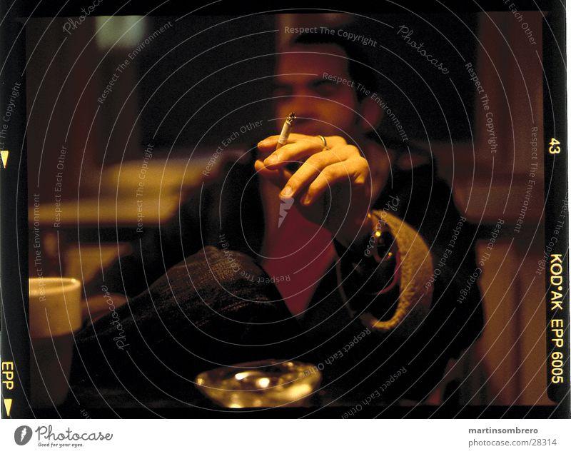 rauchen Aschenbecher gemütlich Mann hand die eine zigarette hält tiefenunschärfe Rauchen Abend Innenaufnahme